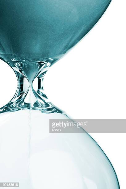Close-up of blue-toned sand in an hourglass