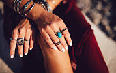 Close-up of young woman's hands with freckles and boho style rings and bracelets