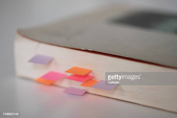 Close-up of book with colorful bookmarks on table