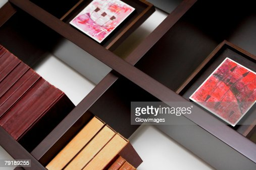 Close-up of books and picture frames in shelves : Foto de stock