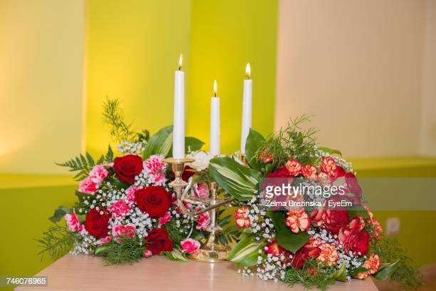 Close-Up Of Bouquet And Candles On Centerpiece