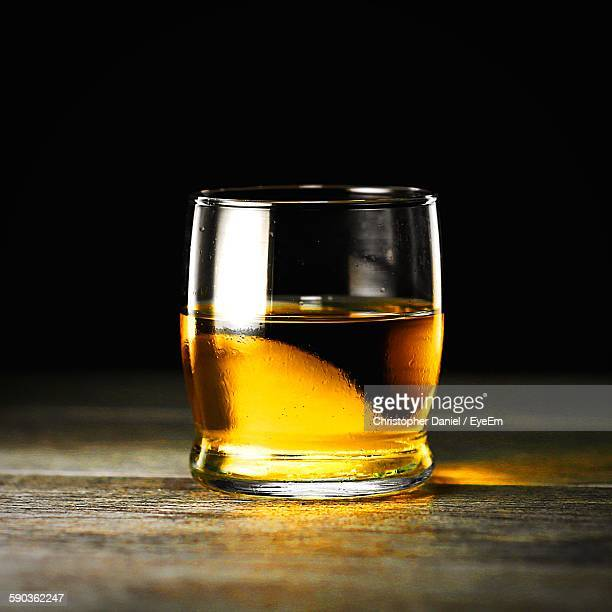 Close-Up Of Bourbon Whiskey On Table Against Black Background