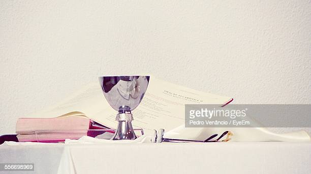 Close-Up Of Bowl Of Holy Water And Book On Table