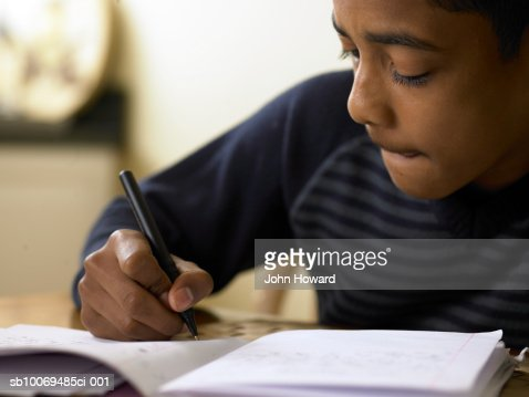 Close-up of boy (12-13) doing homework at desk : Stock Photo