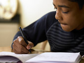 Close-up of boy (12-13) doing homework at desk