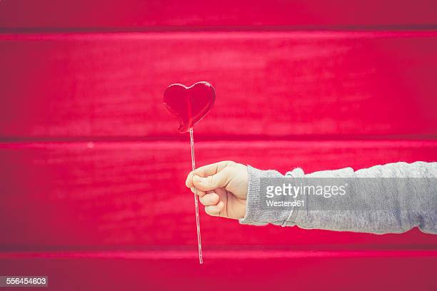 Close-up of boy holding heart-shaped lollipop in front of red wall