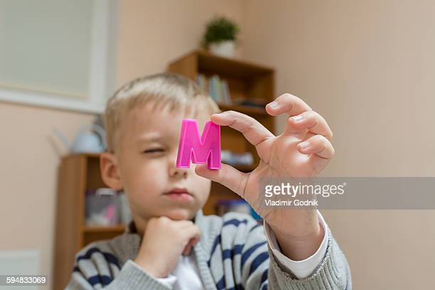 Close-up of boy holding letter M