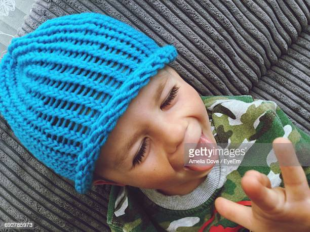 Close-Up Of Boy In Blue Knit Hat Sticking Out Tongue On Sofa At Home