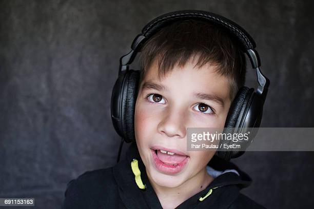 Close-Up Of Boy Listening Music In Headphones Against Wall