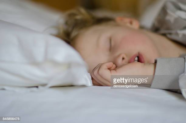 Close-up of boy sleeping in bed