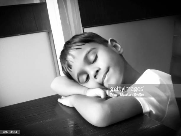 Close-Up Of Boy Sleeping On Table At Home