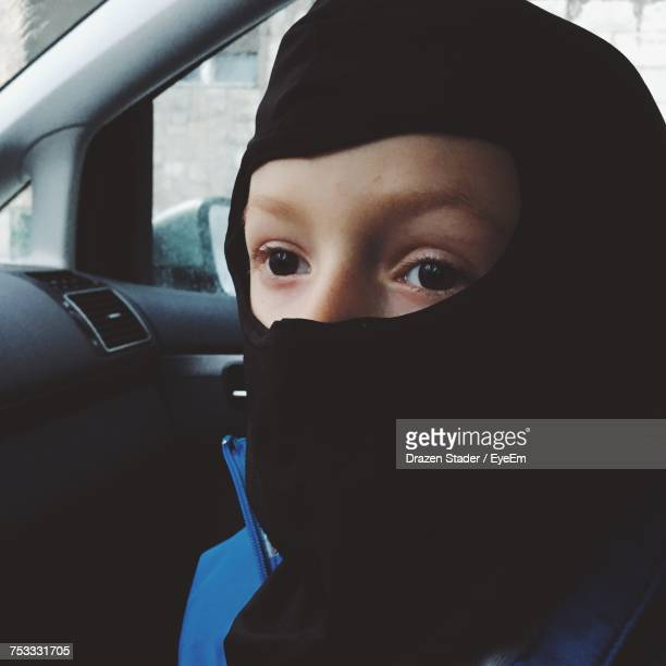 Close-Up Of Boy Wearing Ninja Mask Looking Away While Sitting On Car