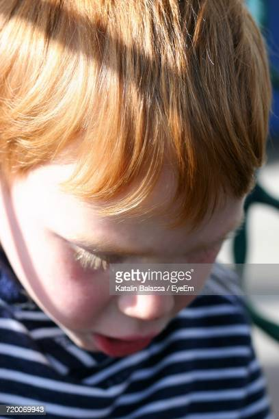 Close-Up Of Boy With Brown Hair Looking Down On Sunny Day