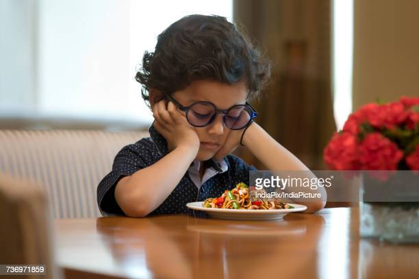 Close-Up of boy with noodles plate on table