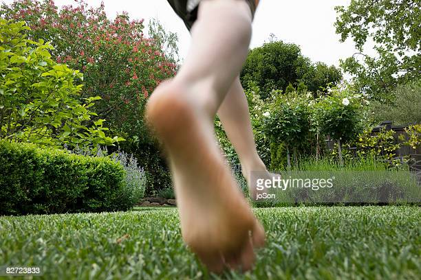 Close-up of boys feet running on lawn