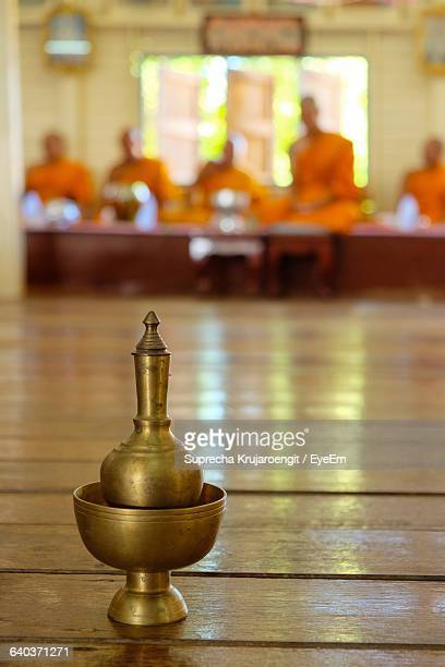 Close-Up Of Brass Incense Stick Holder With Buddhist Monks In Background