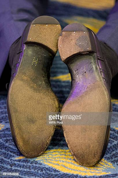 A closeup of brass shoe tacks forming the letter 'H' on the soles of Britain's Prince Harry's shoes as he kneels to speak with award winners whilst...