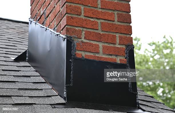 Close-Up Of Brick Chimney On House Roof With medal flashing