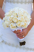 Close-up of bride holding bouquet of flowers
