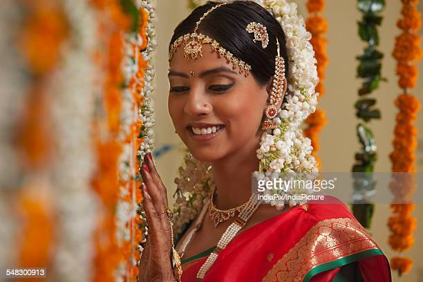 Close-up of bride standing by garlands