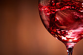 Close-up of brightly red wine poured in the wineglass and abstract splashing against brown background. Macro and horizontal photo. Luxury lifestyle. Still-life and background. Sommelier and degustatio
