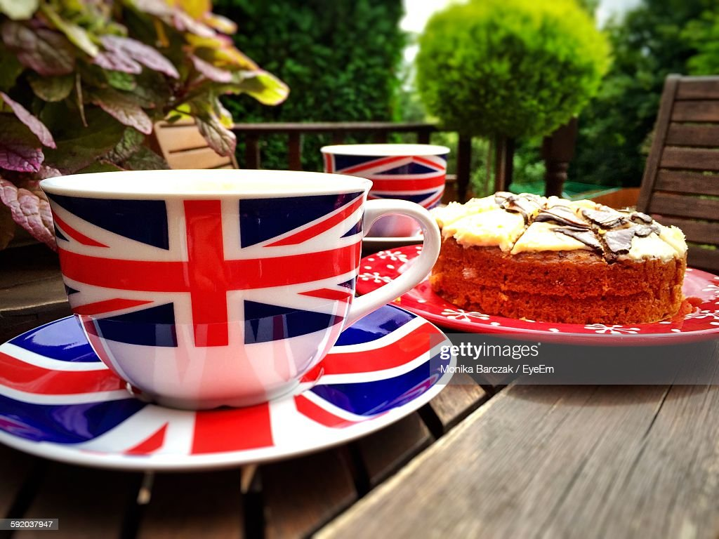 closeup of british flag coffee cups by cake on table stock photo