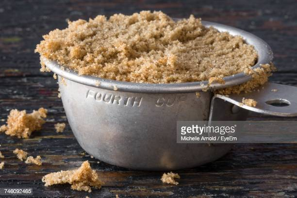 Close-Up Of Brown Sugar In Measuring Cup On Wooden Table
