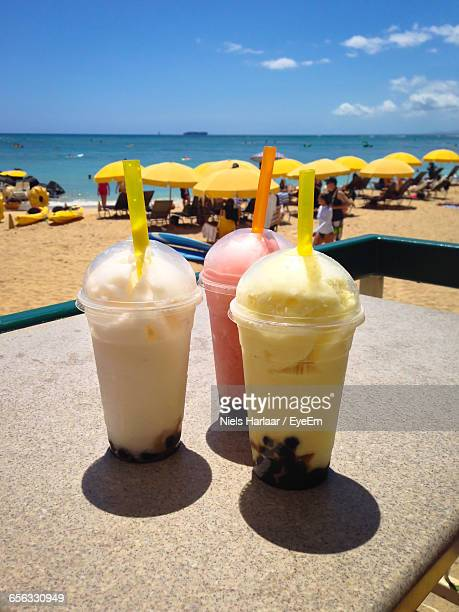 Close-Up Of Bubble Tea In Disposable Glasses On Table At Beach