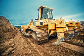 close-up of bulldozer or excavator working with soil on highway construction site