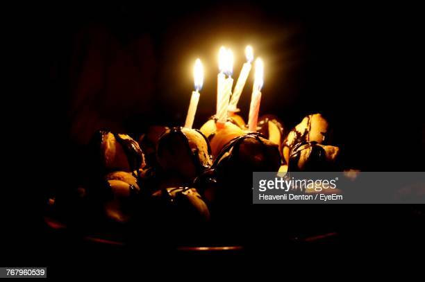Close-Up Of Burning Candles On Birthday Cake In Darkroom