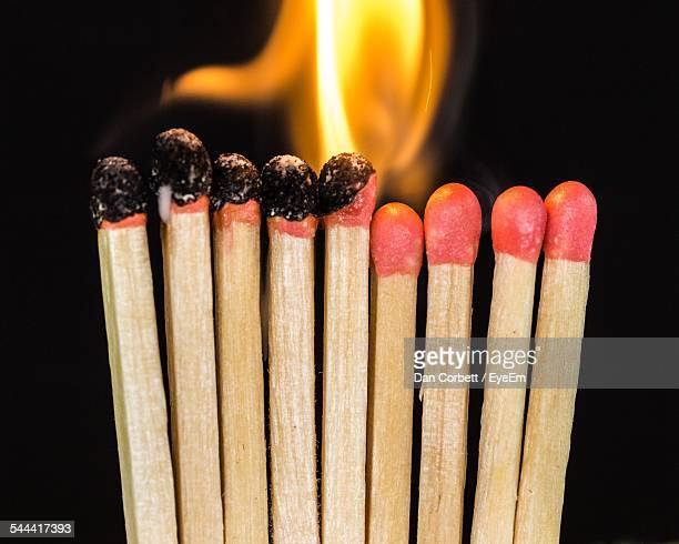 Close-Up Of Burning Matchsticks Against Black Backgrounds