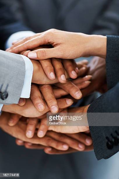 Close-up of business colleagues stacking hands in unity