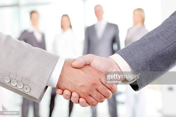 Close-up of business people`s arms handshaking.