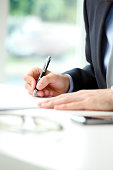 Close-up of businessman sitting at office and fill the form. (signing contract). Business people.