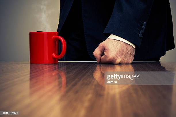 Close-up of Businessman Hitting Desk with Fist Beside Coffee Cup