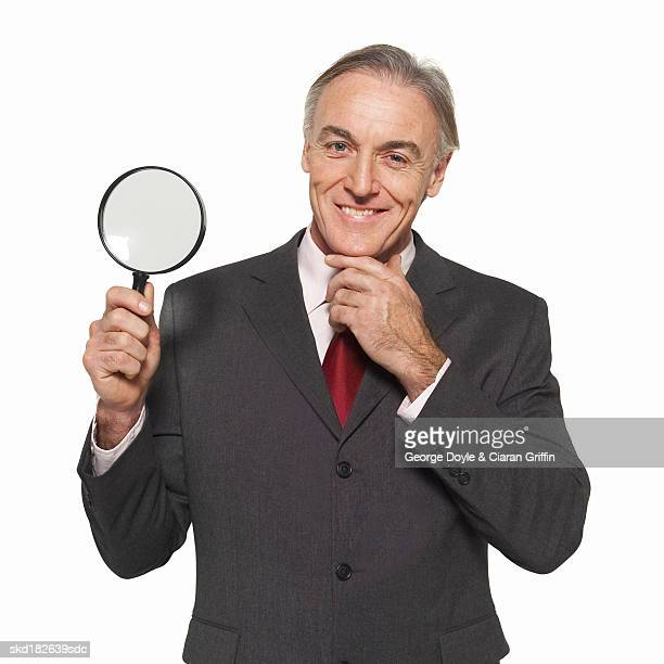 Close-up of businessman holding magnifying lens