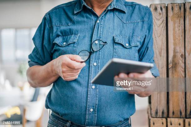 Close-up of businessman holding tablet in office
