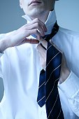Close-up of businessman tying his tie
