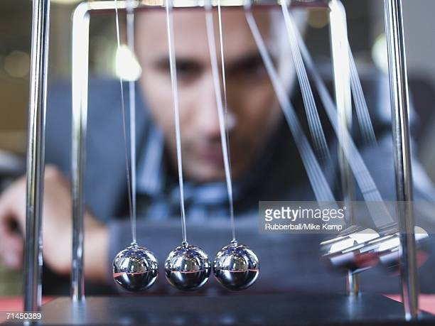 Close-up of businessman watching a Newton's cradle