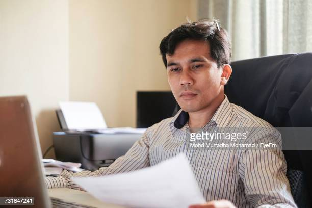 Close-Up Of Businessman Working At Desk In Office