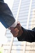 Close-up of businessmen handshake, outdoors