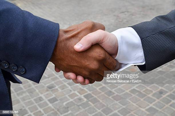 Close-Up Of Businessmen Shaking Hands At Street