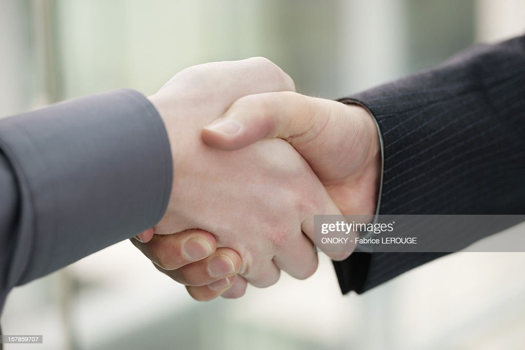 Close-up of businessmen shaking hands in an office