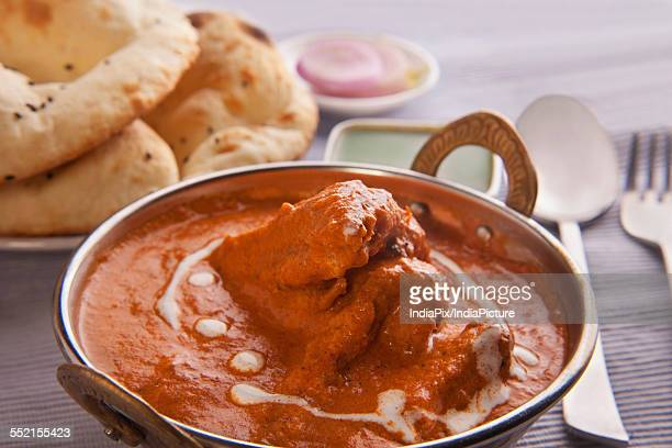 Close-up of butter chicken garnished with cream