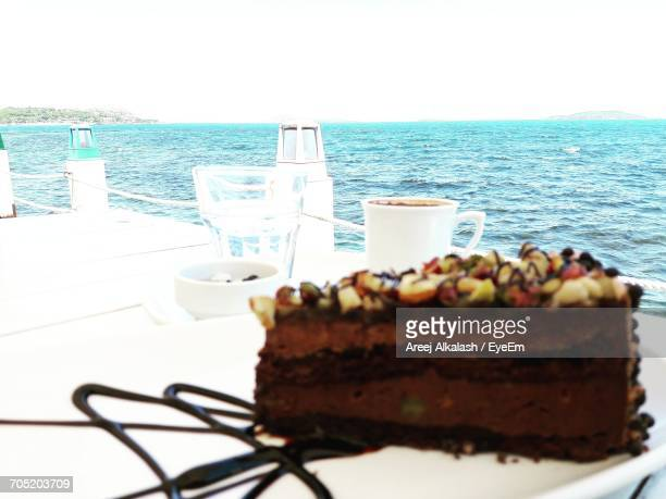 Close-Up Of Cake Slice And Coffee On Table At Restaurant At Beach