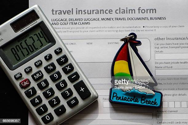 Close-Up Of Calculator And Travel Insurance Form