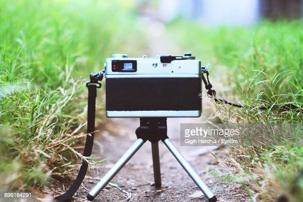 Close-Up Of Camera On Tripod Amidst Grass