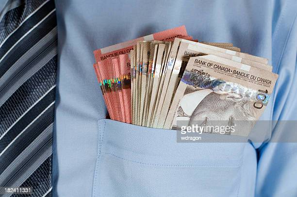A close-up of Canadian money in a shirt pocket