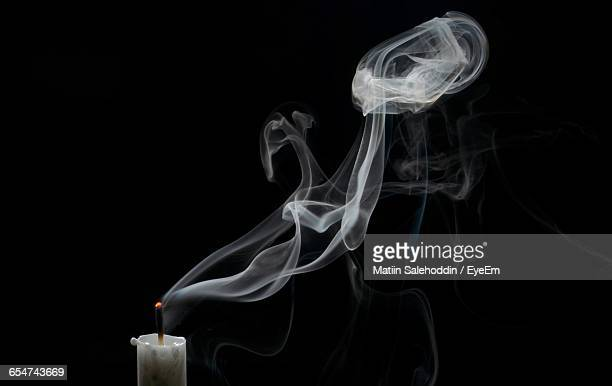 Close-Up Of Candle With Smoke Over Black Background