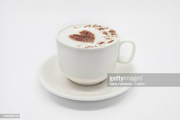 Close-Up Of Cappuccino With Heart Shape Froth Art Against White Background